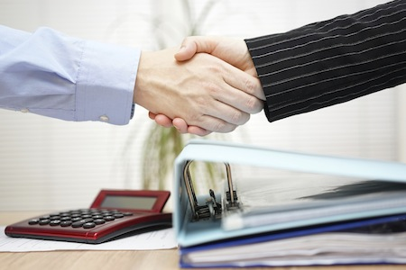 businessman and businesswoman are handshaking over binders