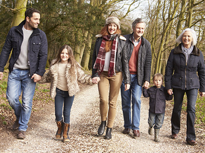 Happy family walking along a dirt road in fall.