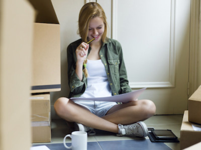 woman looking at forms while moving into a new place