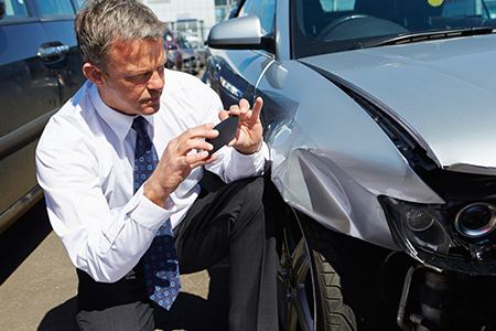 A Man Taking a Photo of His Smashed Bumper for His Car Insurance Company