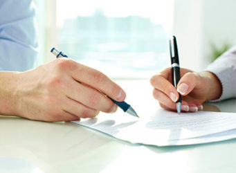 Husband and Wife Signing Life Insurance Document
